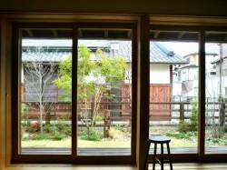 部屋から木製建具越しに庭を見る